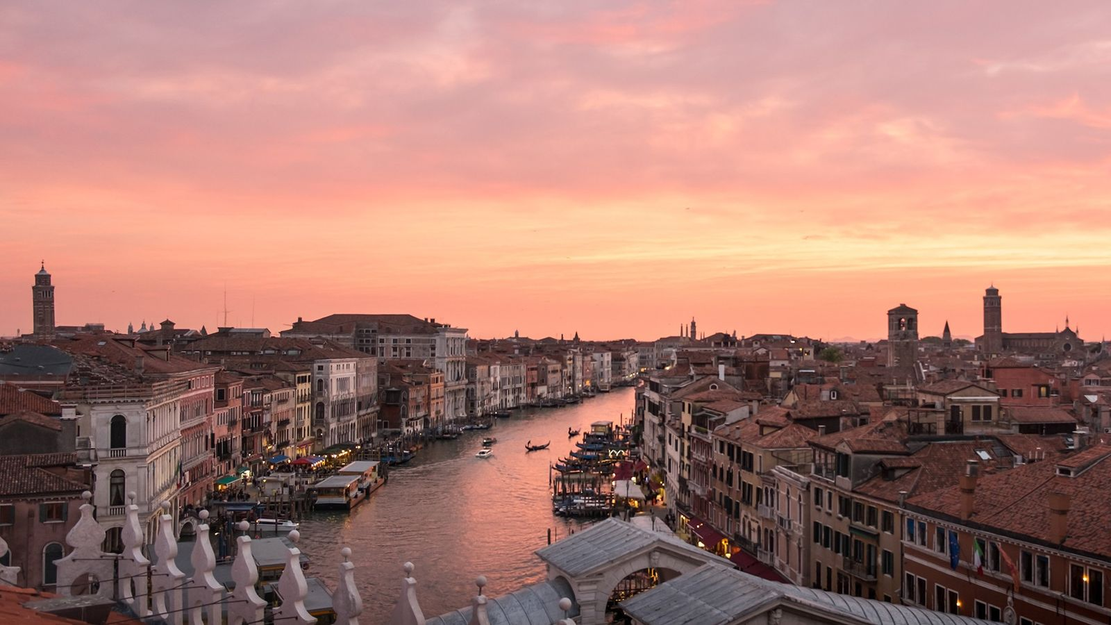 Gondolas cruise down a canal in Venice below a pink-painted sky.