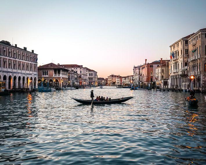A sandolo boat, similar to the iconic gondola, floats across the Grand Canal.