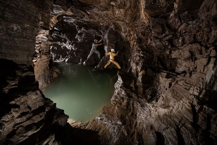 Zverev and Sizikova climb around a deep pool of water in one of the cave's side ...