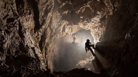 Two cavers make their way through the shaft where, approximately a week later, water suddenly plummeted ...
