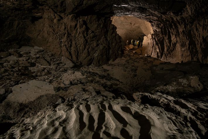 The team of Russian explorers stop for a discussion past a large chamber. The sand on ...