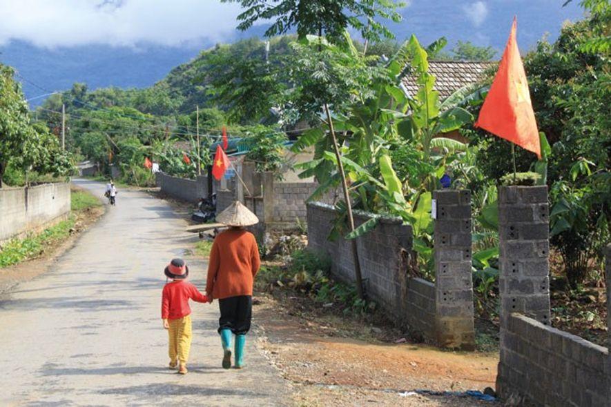 A woman in a nón lá hat walks through a village near Muong Lay. Image: Ben ...