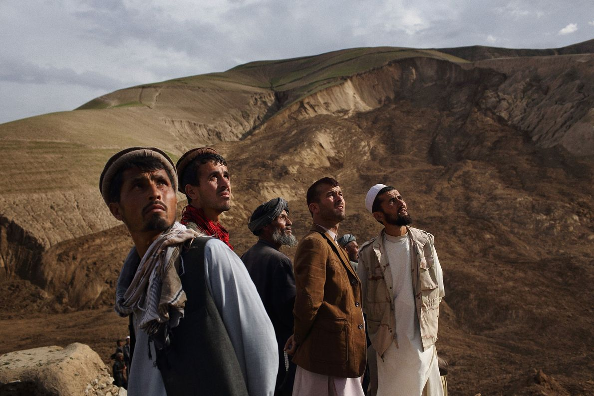 Villagers watch as an army helicopter flies over the site of two landslides in Badakhshan Province ...