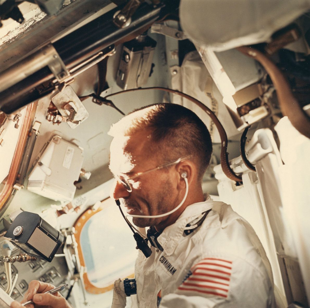 A 70mm Hasselblad camera floats over astronaut Walter Cunningham's right hand on Apollo 7. This photo ...