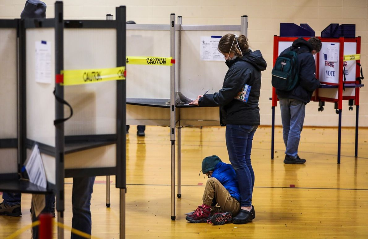 A boy sits under a polling booth while his mom votes in Portland, Maine, on November ...