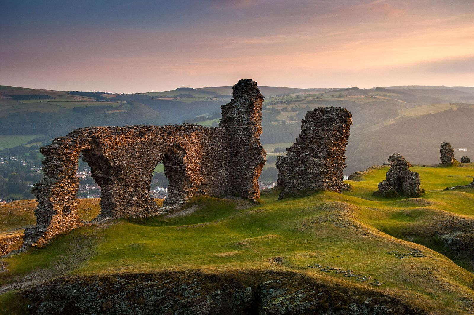 The ruins of the medieval Castell Dinas Bran tower above the Dee Valley and the bustling ...