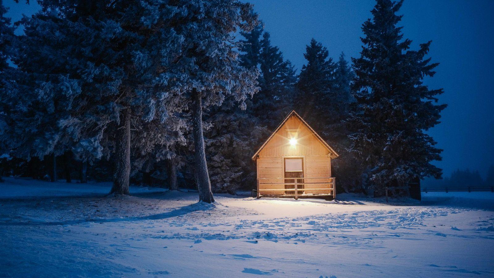 As night draws in, a warm glow illuminates one of Rogla's rustic mountain huts.