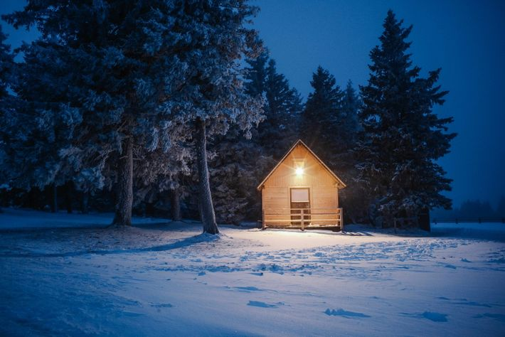 As night draws in, a warm glow illuminates one of Rogla's rustic mountain huts.