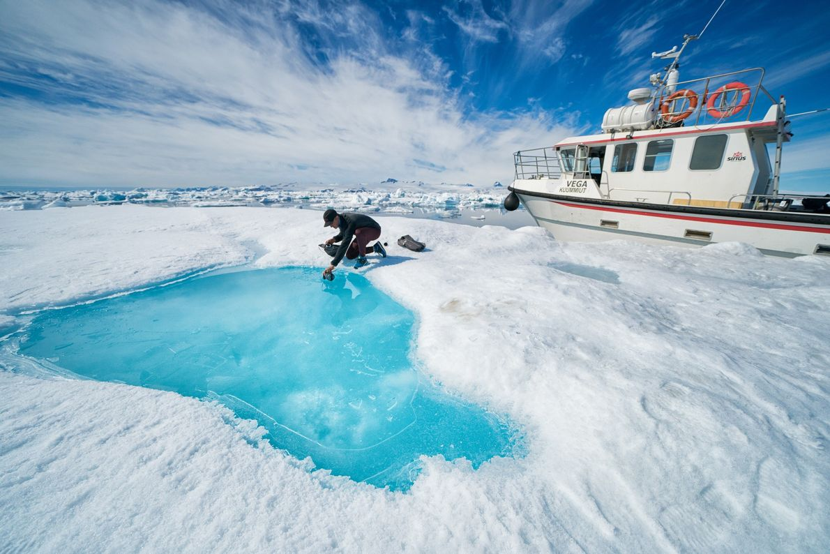 Libecki fills his water bottle from an iceberg's pool of melted water. Despite floating in saltwater, ...
