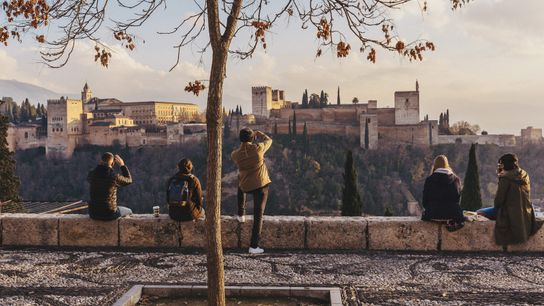 Travellers watch the sunset over the Alhambra from the Mirador San Nicolás.