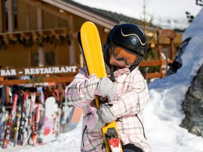 A kid holding a pair of skis outside of a chalet