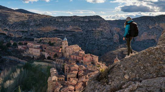 A hiker looks out across the town of Albarracín, near the city of Teruel, Aragon. Spain ...