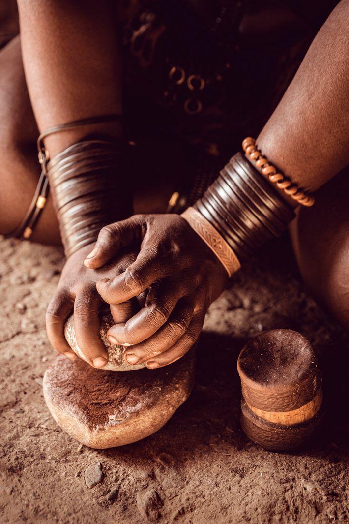 A Himba woman creates otjize, a butter-and-ochre sun cream.