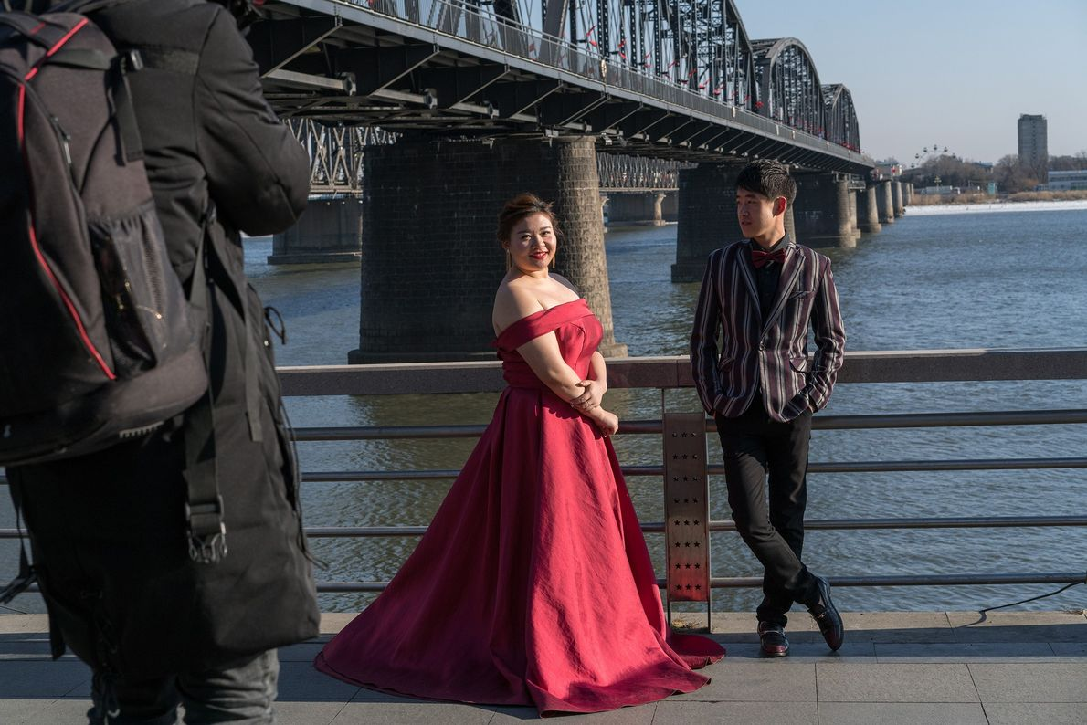 A couple poses for wedding portraits near the Friendship Bridge in Dandong, China.