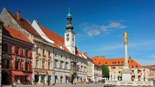 The Maribor Town Hall with a turquoise church spire, andGlavni Trg – a Plague Monument.