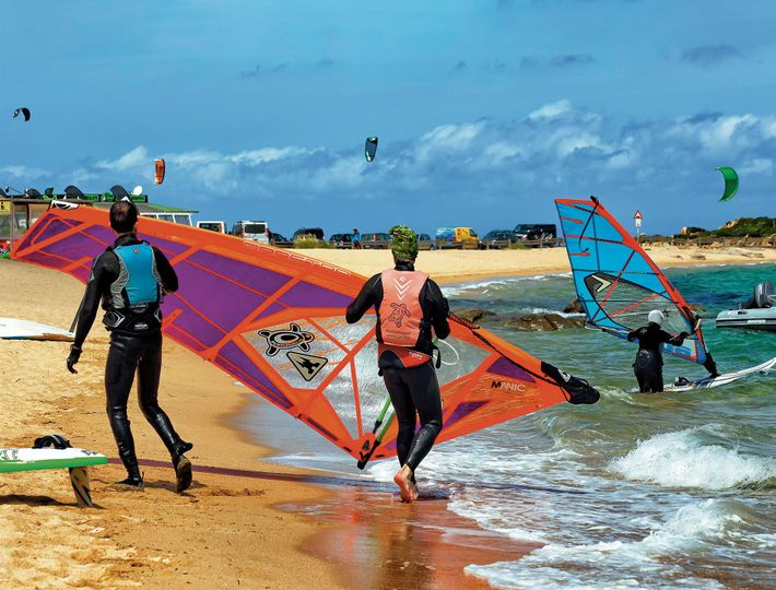 Windsurfers take to the waves at Porto Pollo, a hub for water sports on the island's ...