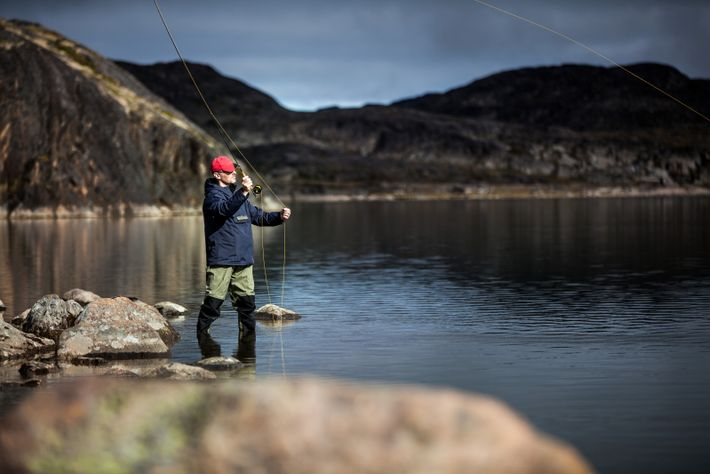 Fly-fishing at Erfalik River. In Greenland, many fishing destinations can only be reached by boat or ...