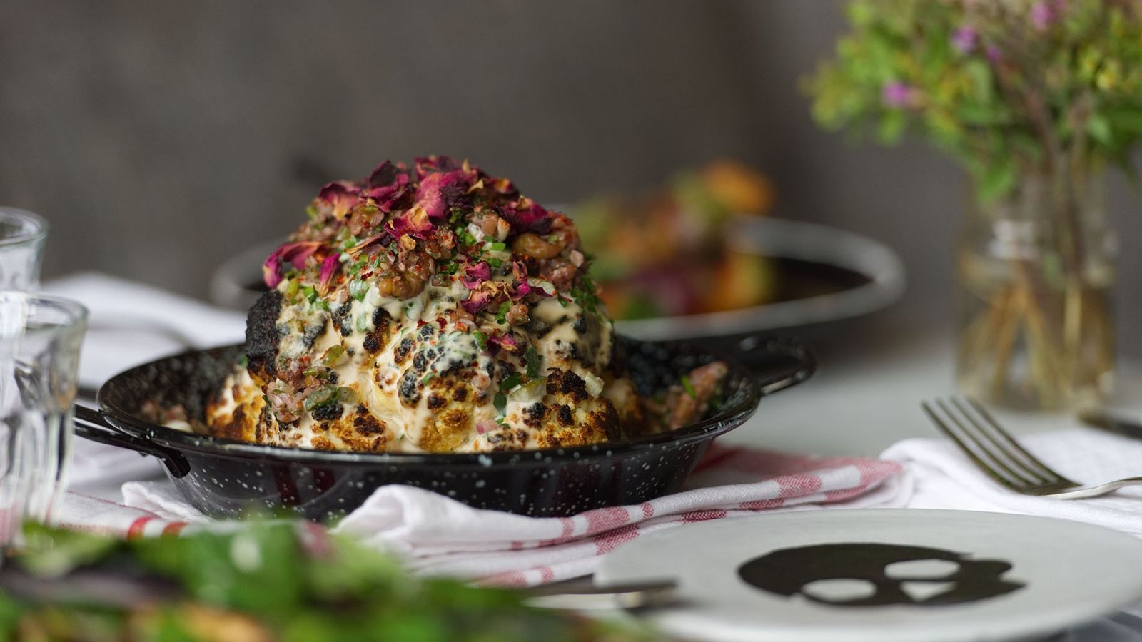 A whole head of cauliflower roasted in a Josper oven and topped with spiced butter, yoghurt-tahini ...