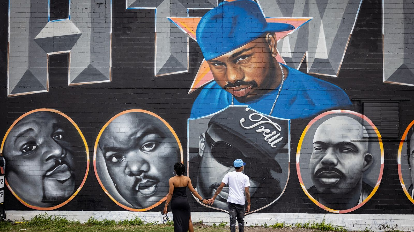 Locals admire the work of artist Article on Downtown's Houston Graffiti Building.