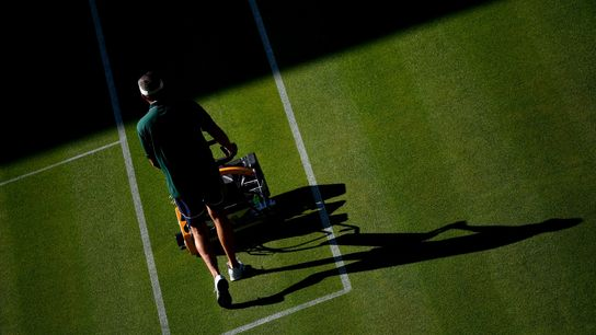 A groundsman cuts the grass on Centre Court at the All England Tennis Club on the ...
