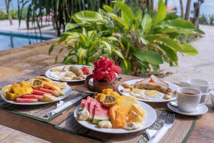 A tropical breakfast consisting of fresh fruit, coffee and fried eggs in Tanzania.