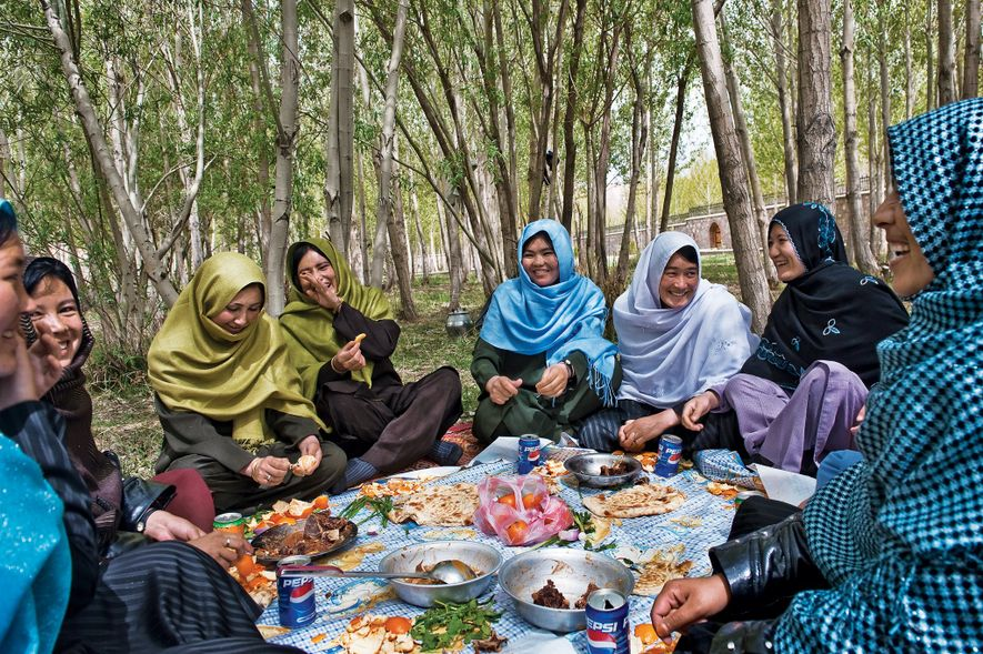 2010, AFGHANISTAN | Women share a meal of flatbread, meats, and fruit in the Women's Garden, ...