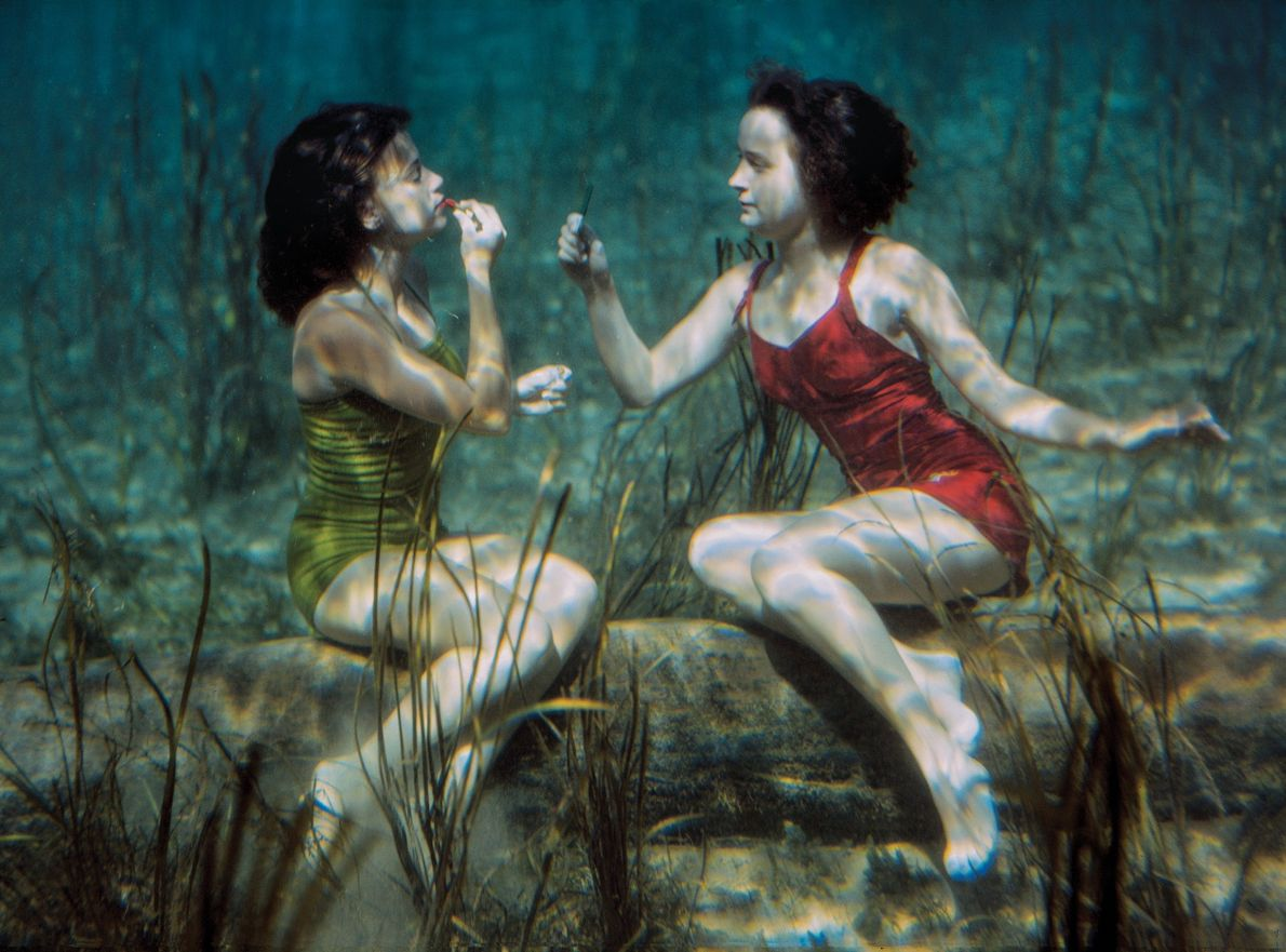 PRE-1944, FLORIDA | Performing swimmers apply lipstick in crystal clear Wakulla Springs, Florida, a popular spot ...