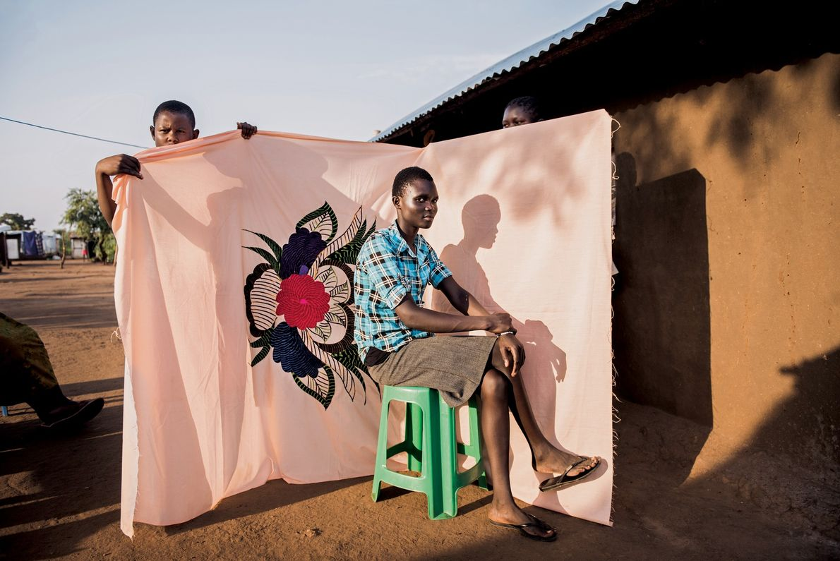 2017, UGANDA   Irene Sonia poses in front of a milaya, or bedsheet—one of the few ...