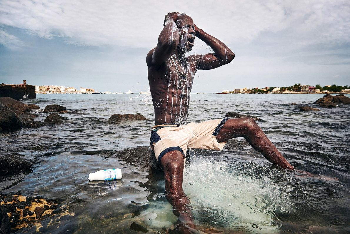 Kherou Ngor, a young wrestling champion, washes himself with milk on the shore of Ngor, Dakar. ...