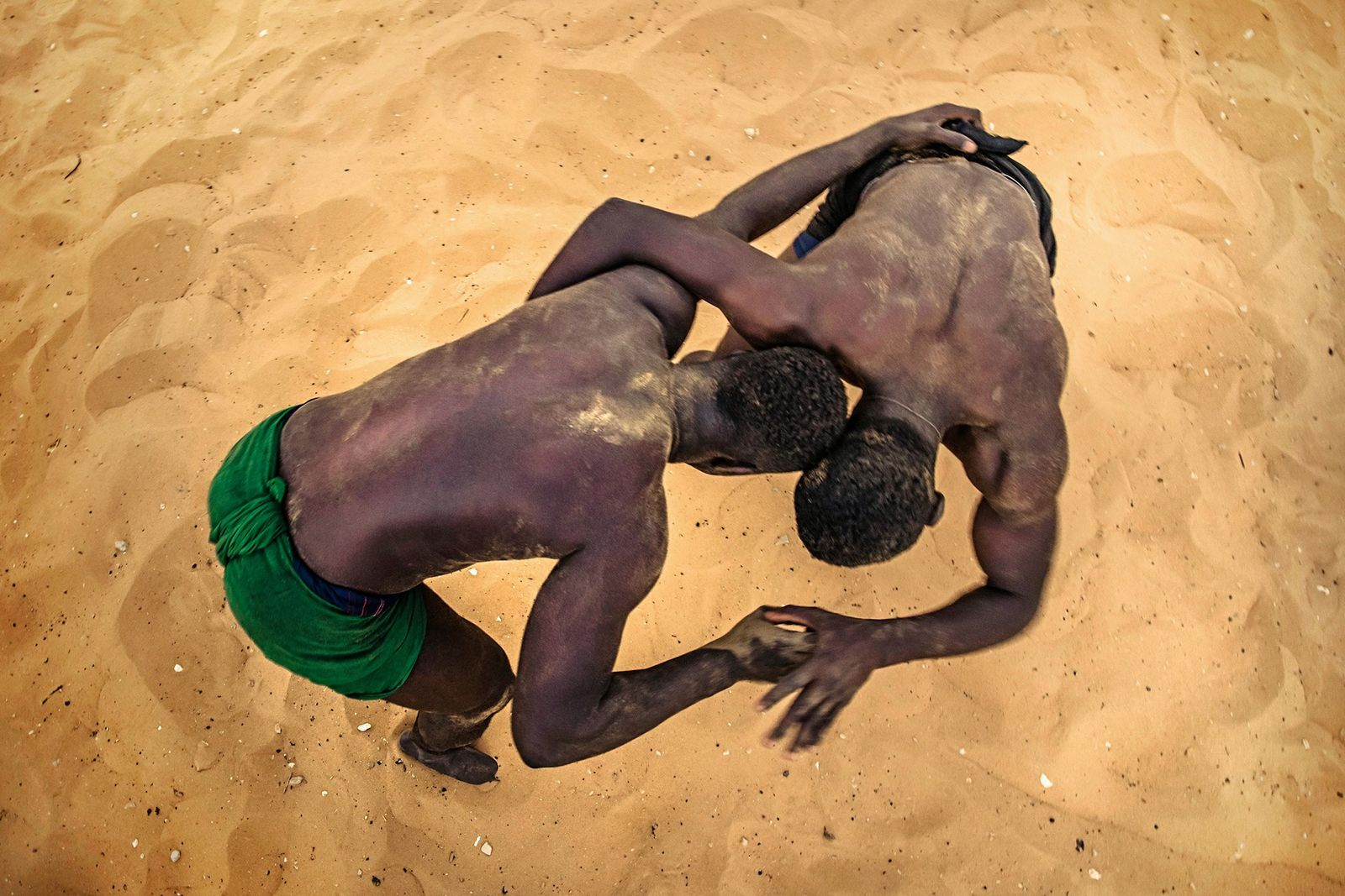 Wrestlers train at a school in Dakar, each trying to unbalance their opponent.
