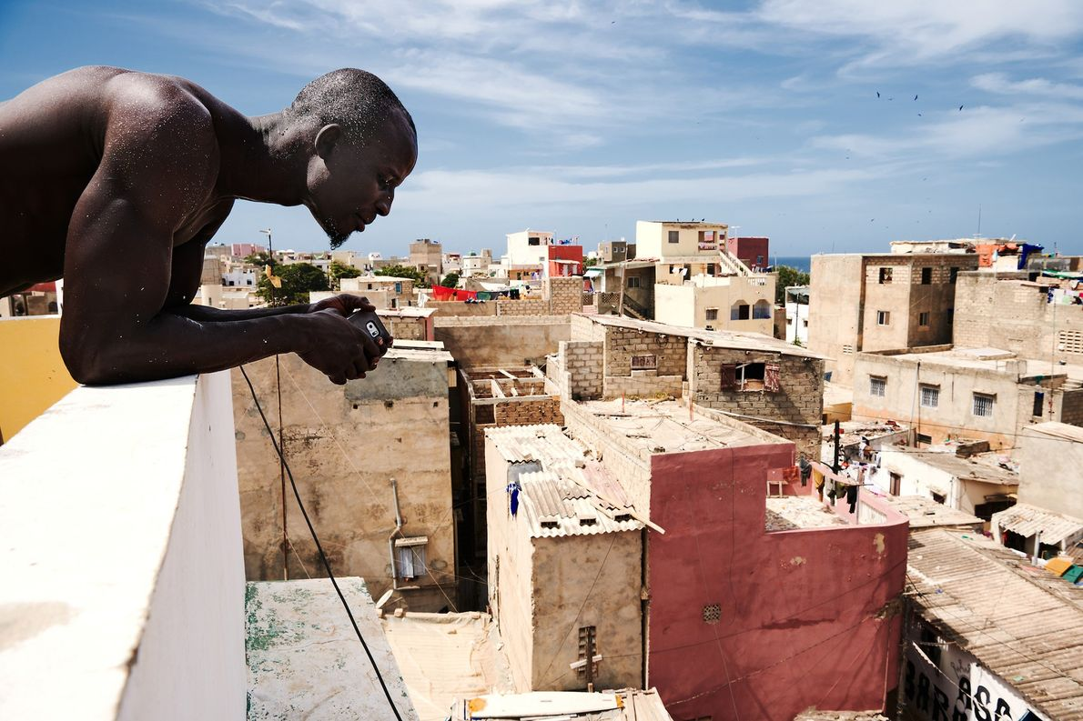Kehrou Ngor looks down at the streets from his family home in the village of Ngor ...