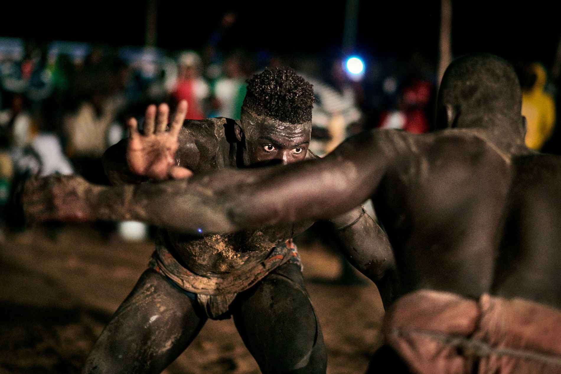 Two wrestlers face off during a local tournament in the region of Sine Saloum.