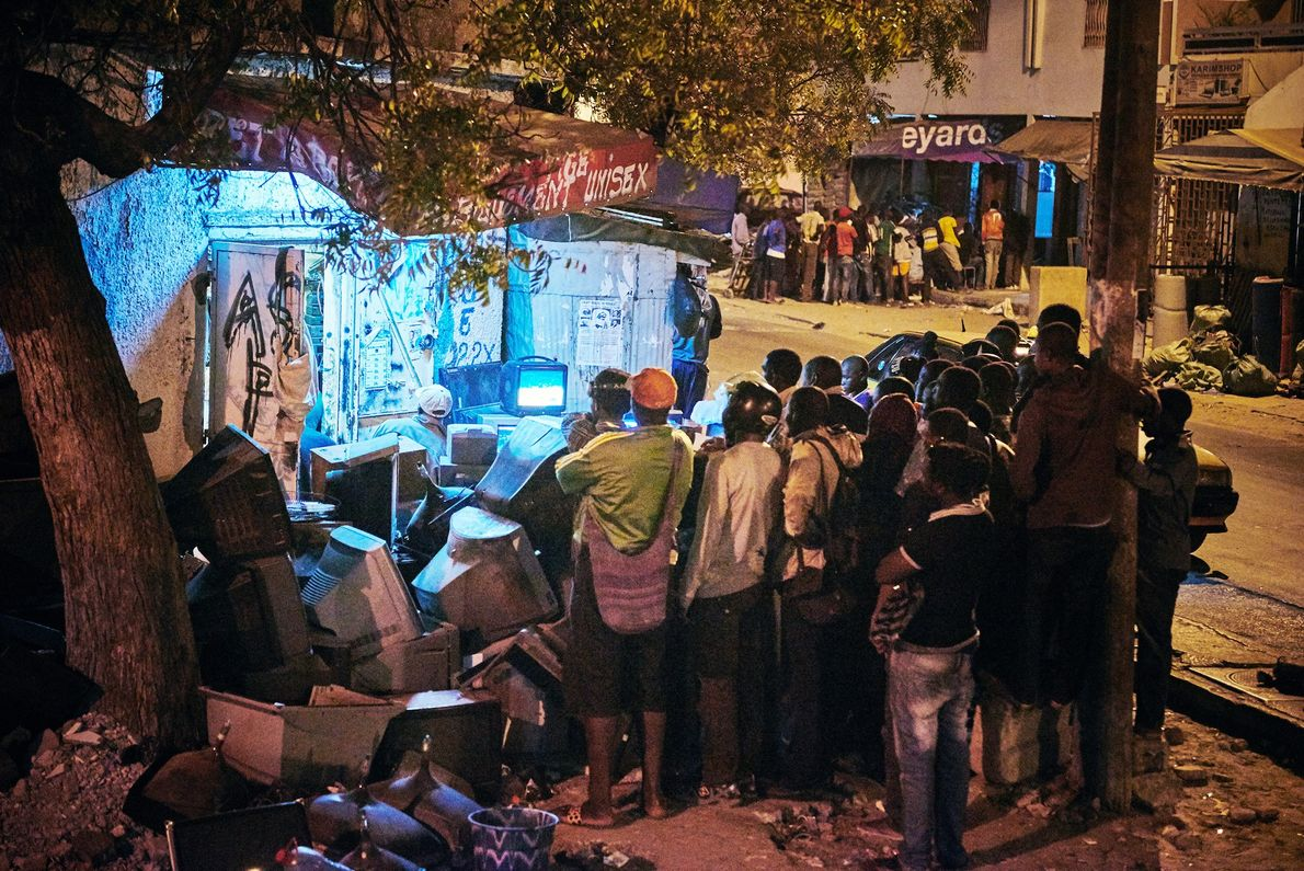 People gather on the streets in Dakar to watch a wrestling match on Independence Day.