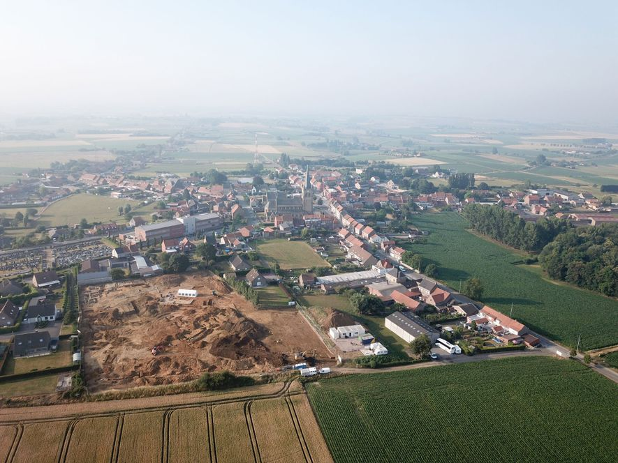 An aerial view of the Dig Hill 80 excavation site with the town of Wijtschate in ...
