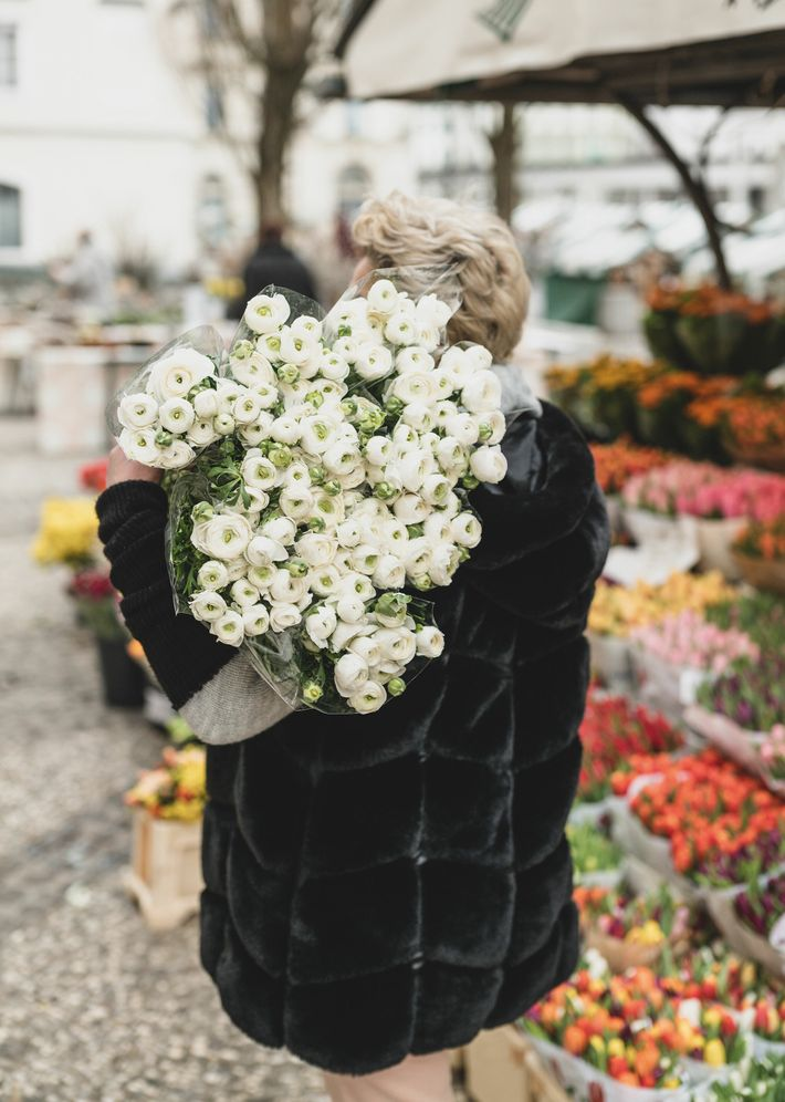 A woman walks with an armful of flowers purchased at the Ljubljana Central Market.