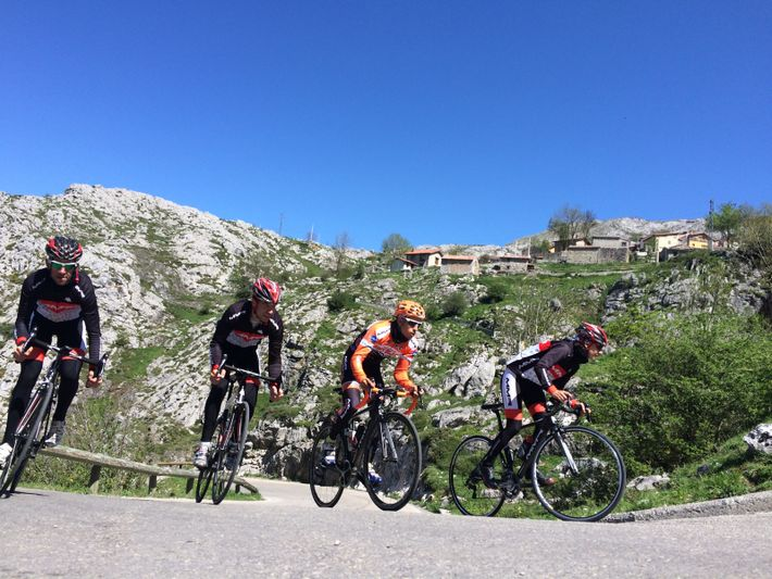 Cyclists climb to Sotres village on a scenic mountain section of the Vuelta a España road ...