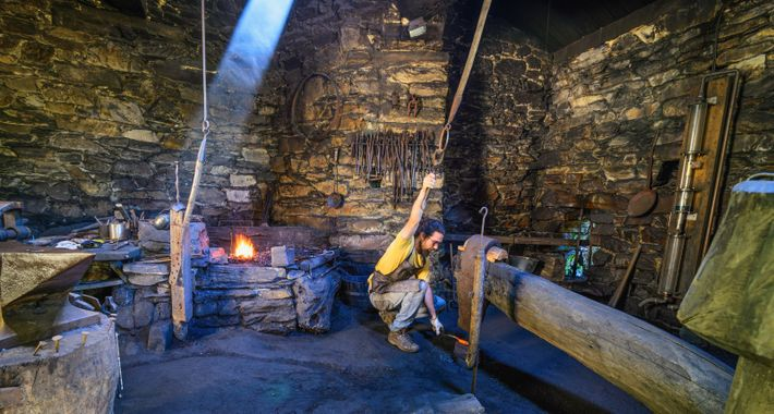 A blacksmith, or ferreiro, demonstrates the traditional tools and methods still used to craft iron at ...