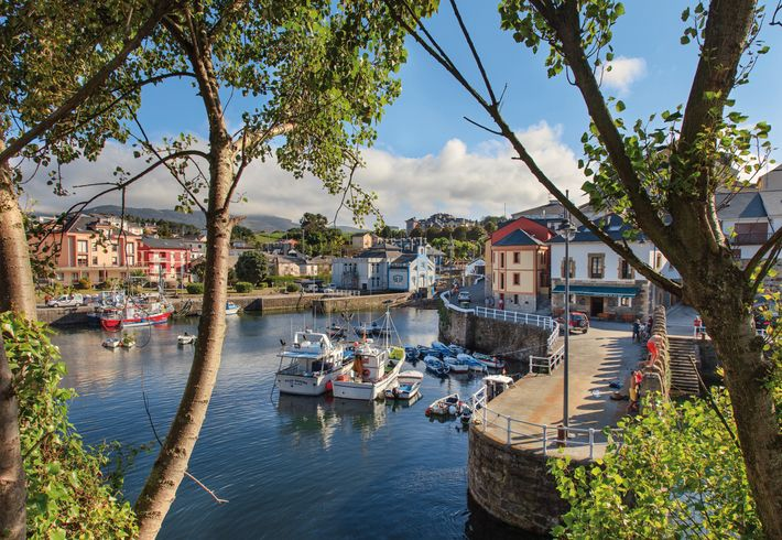 Fishing boats in the tranquil harbour of Puerto de Vega, a traditional Cantabrian seafaring village where ...