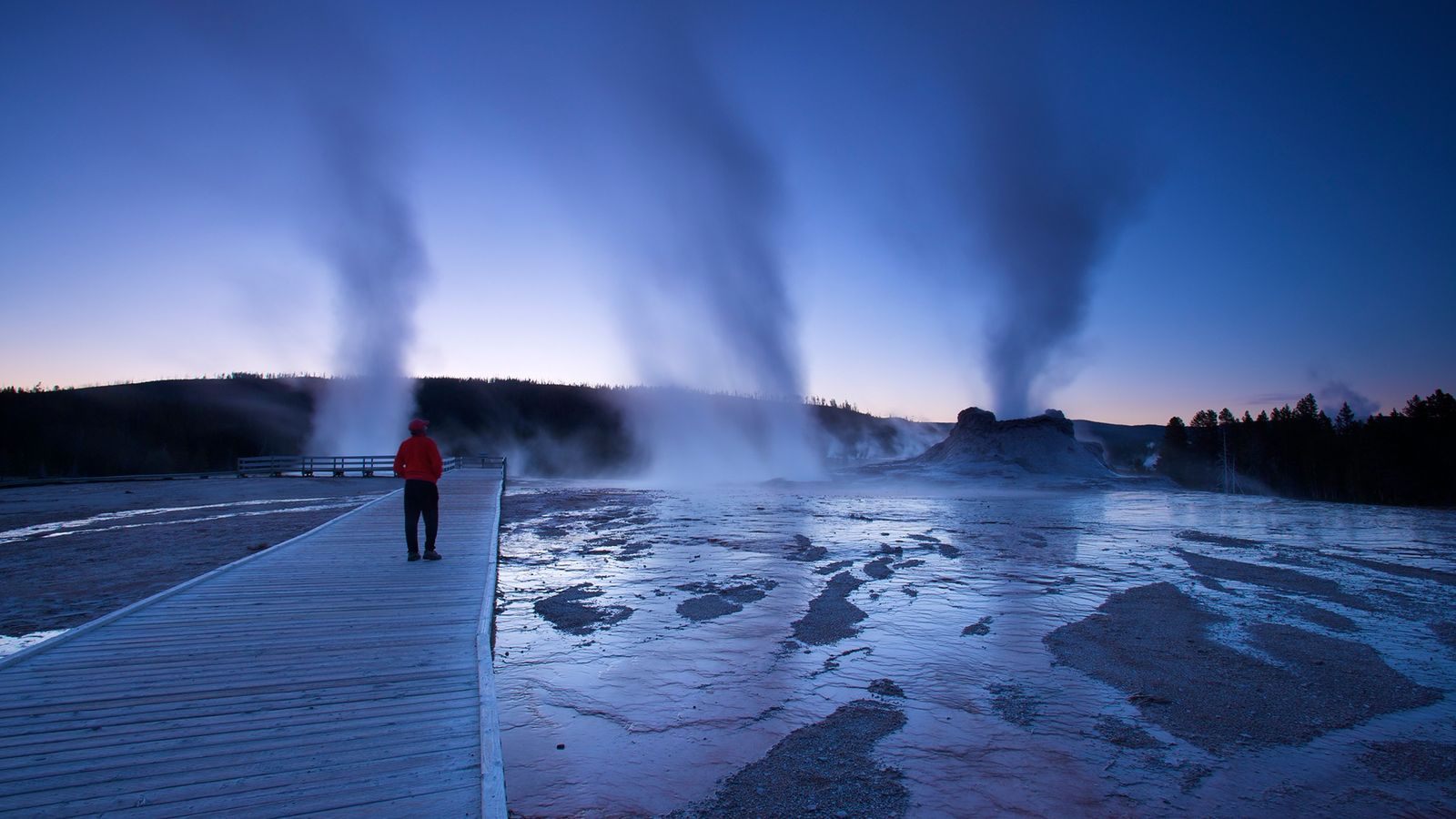 Steam rises at dusk at Castle Geyser in Yellowstone National Park.