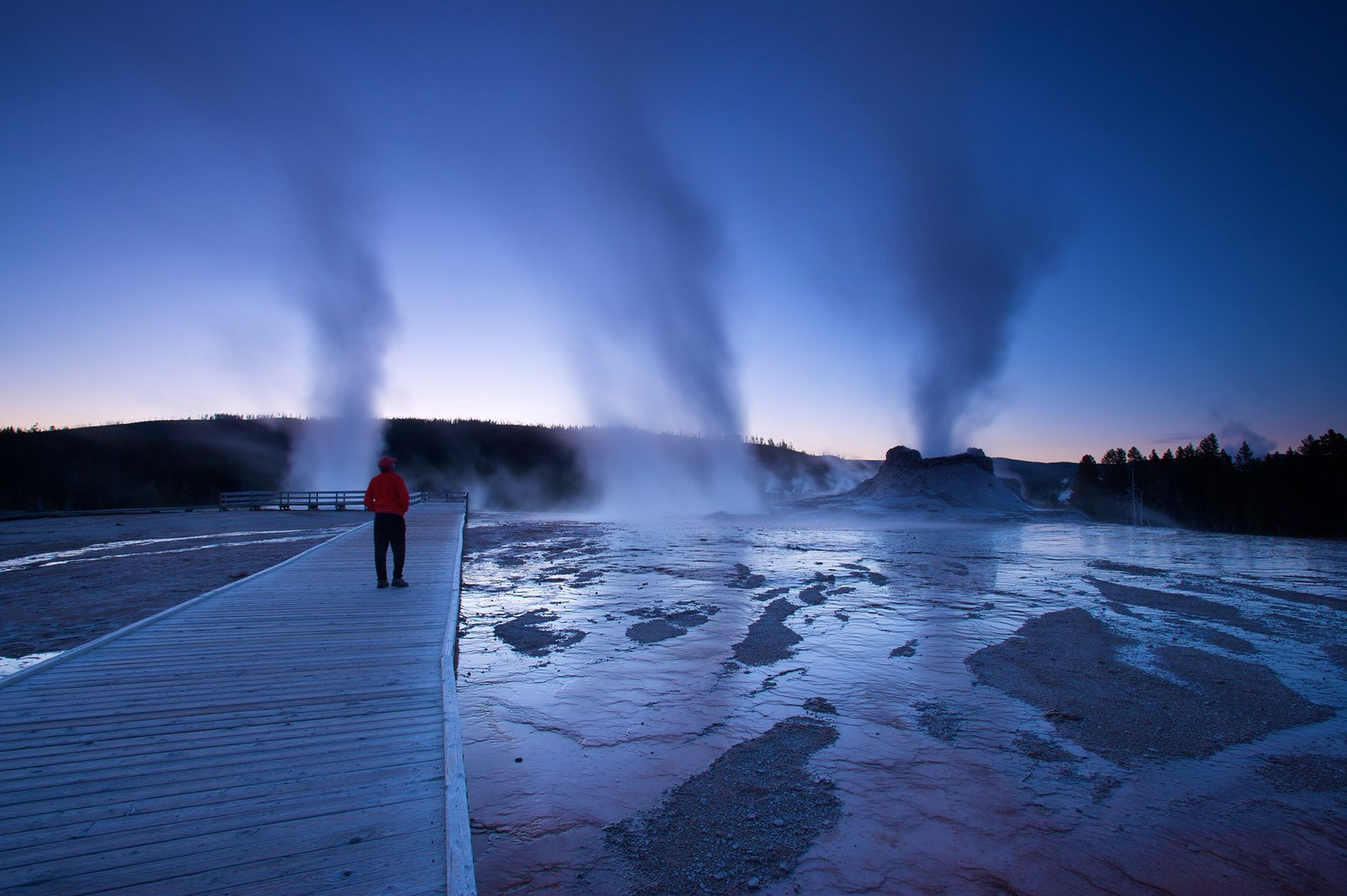 Steam rises at dusk at Castle Geyser in Yellowstone National Park.  ...