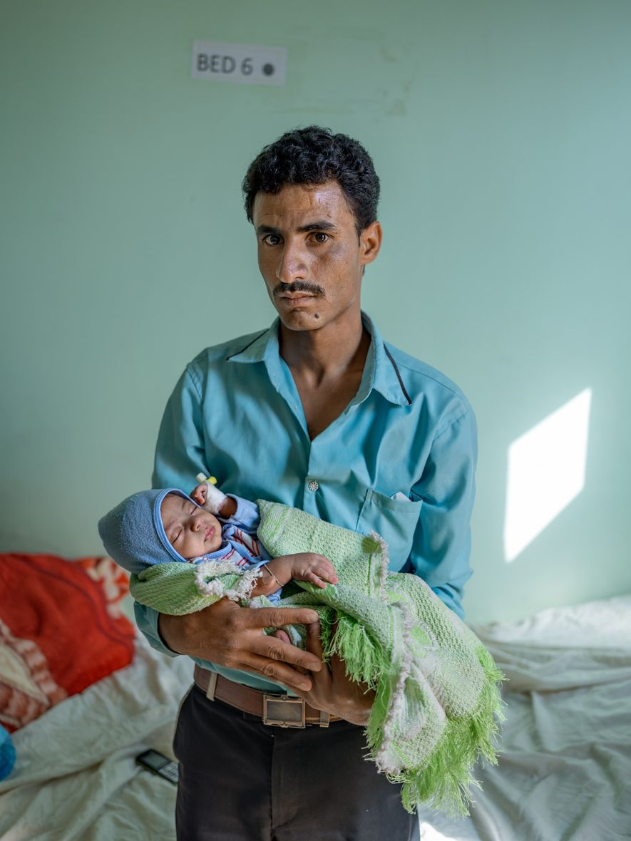 A father holds his baby at the Mother and Child Hospital after the child was treated ...