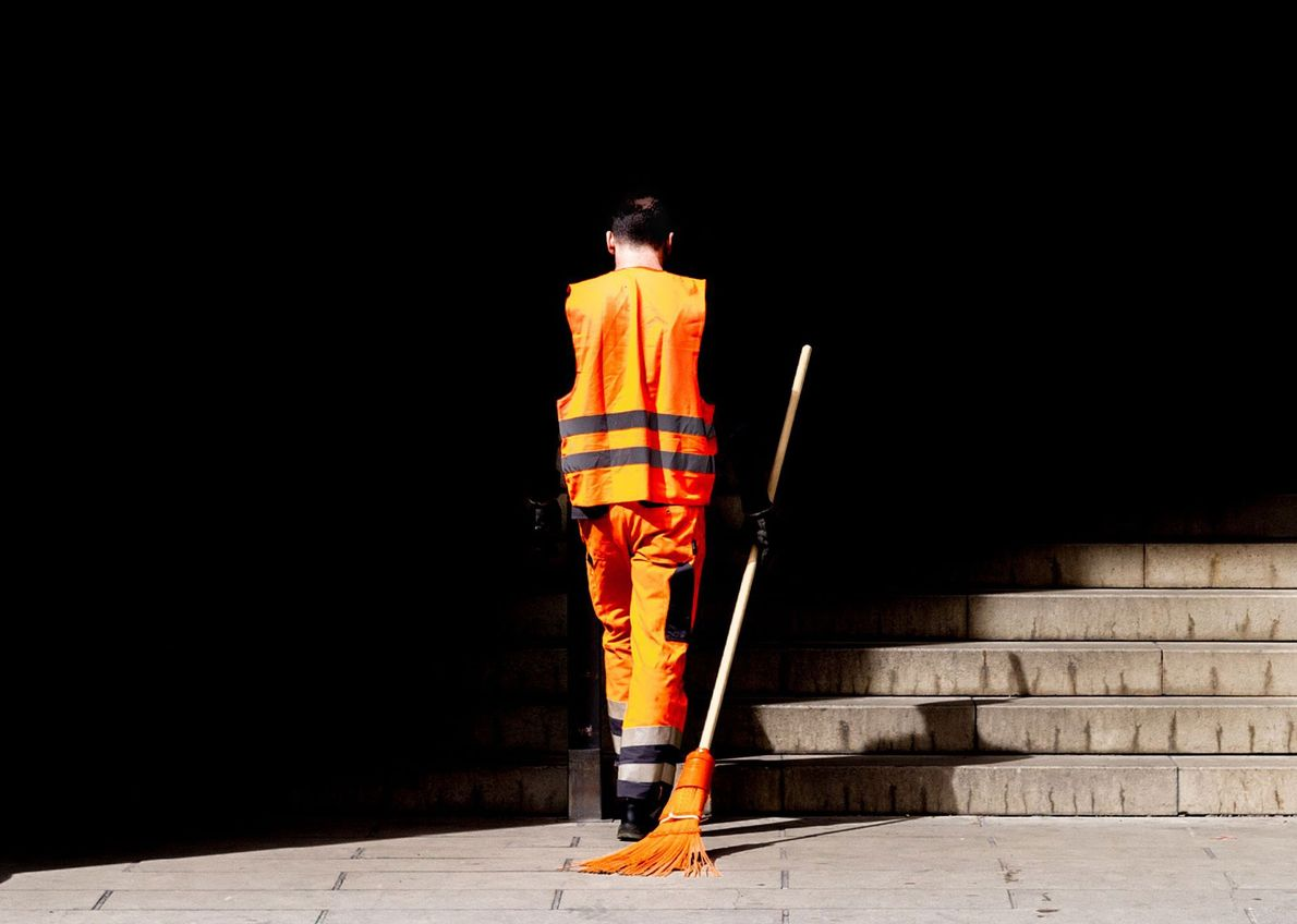 München, Germany  The vibrant orange of a city sanitation worker's uniform and matching broom adds a pop ...