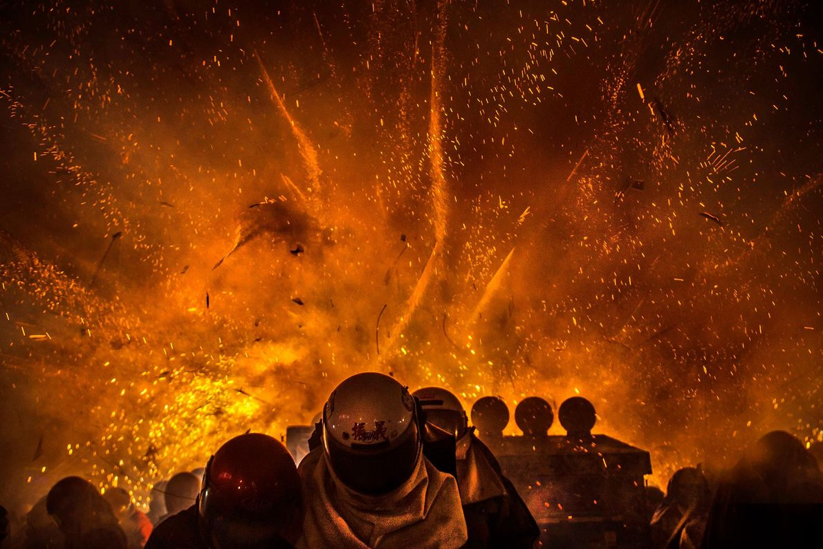 """Taiwan Brave spectators wear helmets as protection as against exploding """"beehives"""" filled with thousands of rockets. Being ..."""