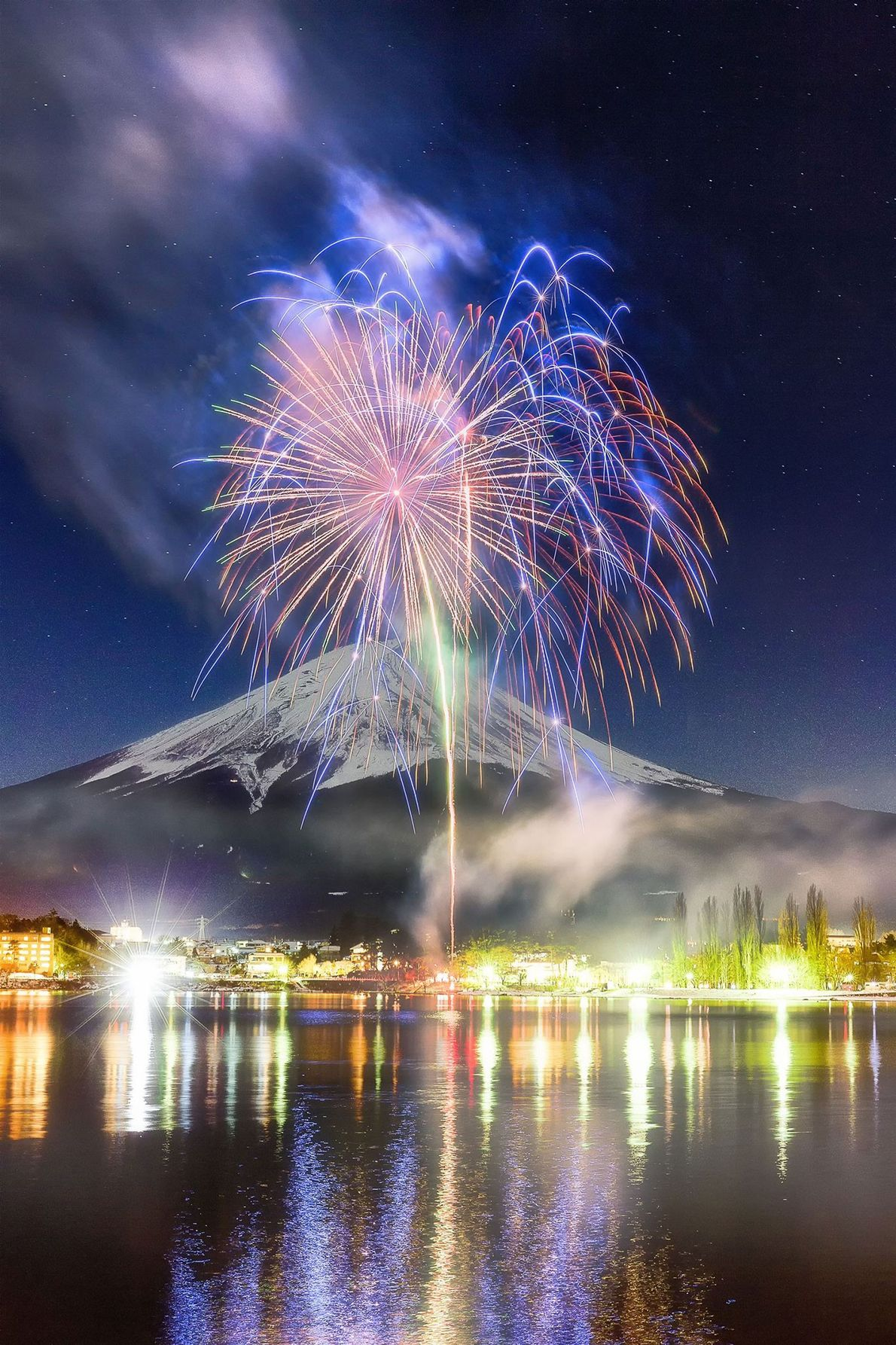 Fuji Bursting in a crisp winter sky, fireworks are reflected in the surrounding water. Aizawa's image offers ...