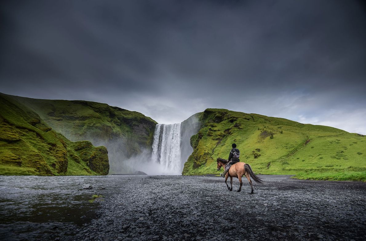 A horseback rider overlooks a broad cascade in Iceland.