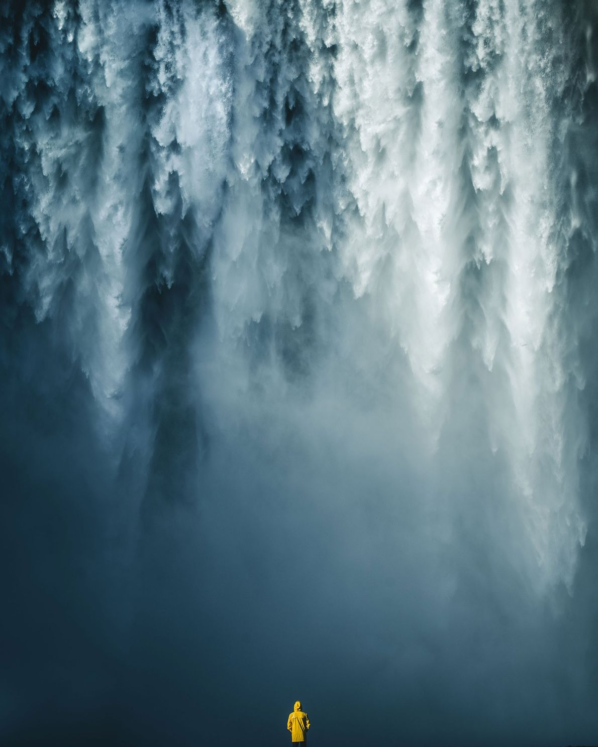 A visitor is dwarfed by the cascading water and mist of one of Iceland's famous waterfalls.