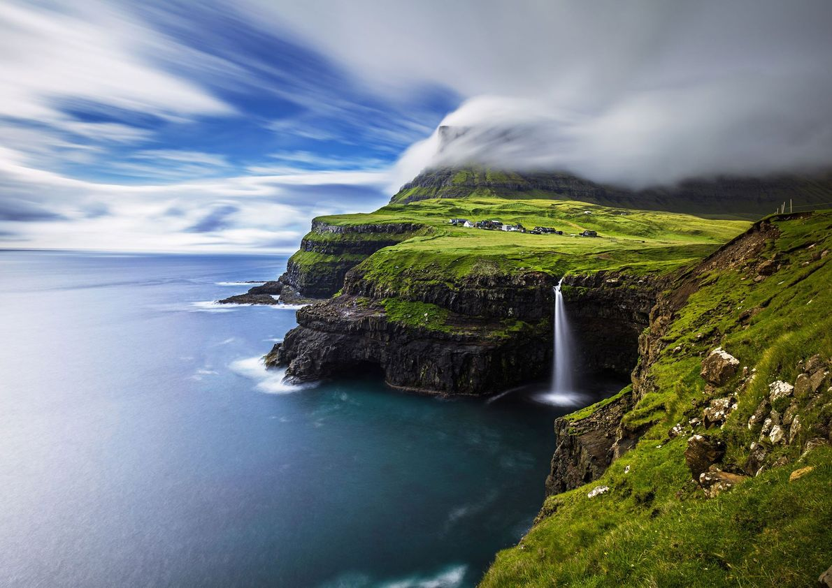 A tall waterfall cascades off a promontory of Vagar, one of the North Atlantic's autonomous Faroe ...