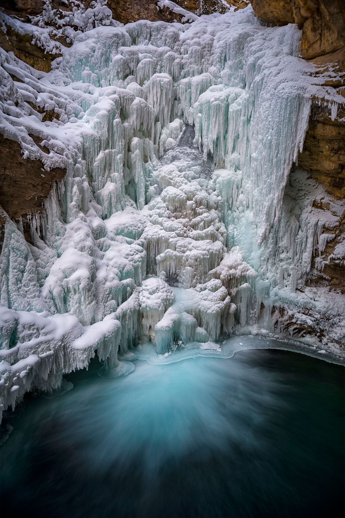 Water still runs beneath the icy shell of this waterfall in Banff National Park.